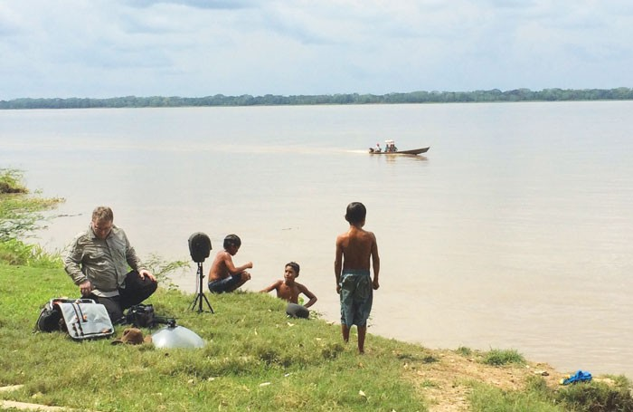 Gareth Fry records on the bank of the Amazon river with members of a Mayoruna community