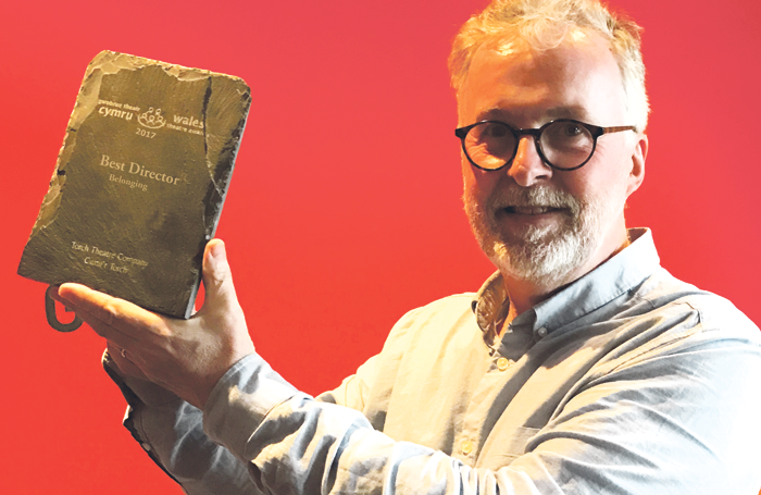 Peter Doran holds the Best Director Award from Wales Theatre Awards for Belonging – a bilingual play about dementia