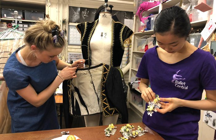 Central dancers remaking costumes